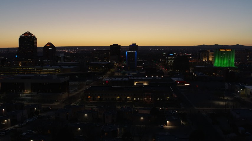 5.7K stock footage aerial video descend past hotel with blue lighting near office towers at twilight, Downtown Albuquerque, New Mexico Aerial Stock Footage | DX0002_123_034