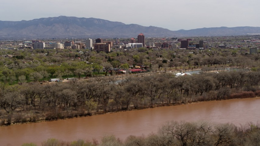 5.7K stock footage aerial video of high-rise office buildings seen while ascending by the Rio Grande, Downtown Albuquerque, New Mexico Aerial Stock Footage | DX0002_124_002