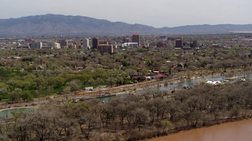5.7K stock footage aerial video approach high-rise office buildings while ascending over the Rio Grande and park, Downtown Albuquerque, New Mexico Aerial Stock Footage DX0002_124_005