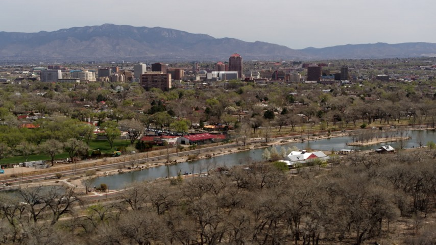 5.7K stock footage aerial video flying by park and Rio Grande with view of high-rise office buildings, Downtown Albuquerque, New Mexico Aerial Stock Footage | DX0002_124_008