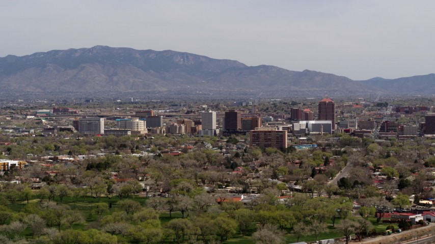 5.7K stock footage aerial video descend with wide view of high-rise office buildings, distant mountains, Downtown Albuquerque, New Mexico Aerial Stock Footage | DX0002_124_019
