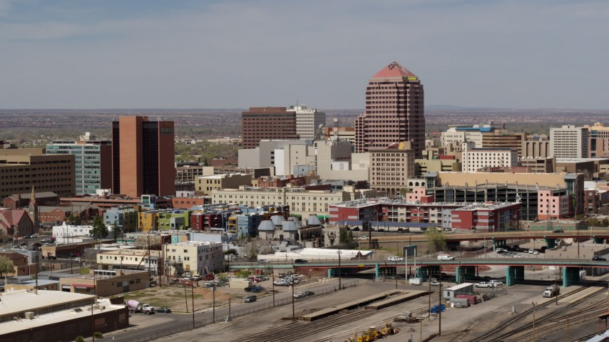 5.7K stock footage aerial video of an office high-rise seen while ascending near train tracks, Downtown Albuquerque, New Mexico Aerial Stock Footage | DX0002_124_021