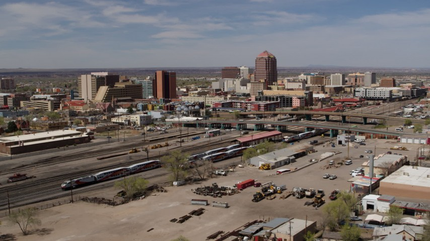 5.7K stock footage aerial video passing railroad tracks with view of Albuquerque Plaza and surrounding buildings, Downtown Albuquerque, New Mexico Aerial Stock Footage | DX0002_124_029