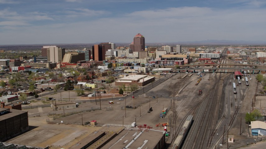 5.7K stock footage aerial video flyby train tracks with office buildings in the background, Downtown Albuquerque, New Mexico Aerial Stock Footage | DX0002_124_032