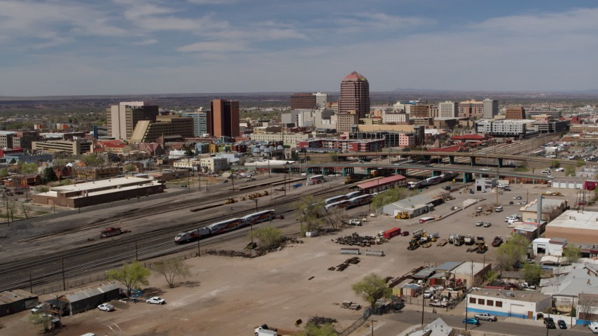 5.7K stock footage aerial video approach train tracks with office buildings in the background, Downtown Albuquerque, New Mexico Aerial Stock Footage | DX0002_124_033