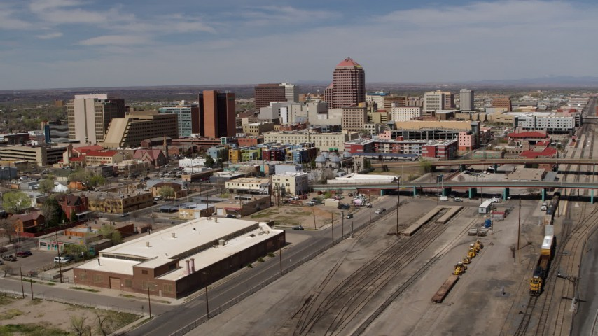 5.7K stock footage aerial video reverse view of train tracks and office buildings in the background, Downtown Albuquerque, New Mexico Aerial Stock Footage | DX0002_124_034