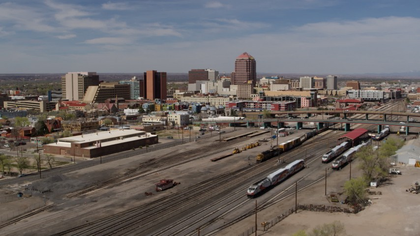5.7K stock footage aerial video fly over train tracks toward office buildings in the background, Downtown Albuquerque, New Mexico Aerial Stock Footage | DX0002_124_035