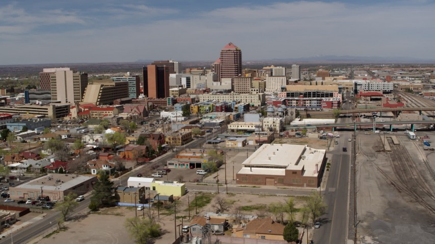 5.7K stock footage aerial video reverse view of office buildings, and flyby railroad tracks, Downtown Albuquerque, New Mexico Aerial Stock Footage | DX0002_124_036