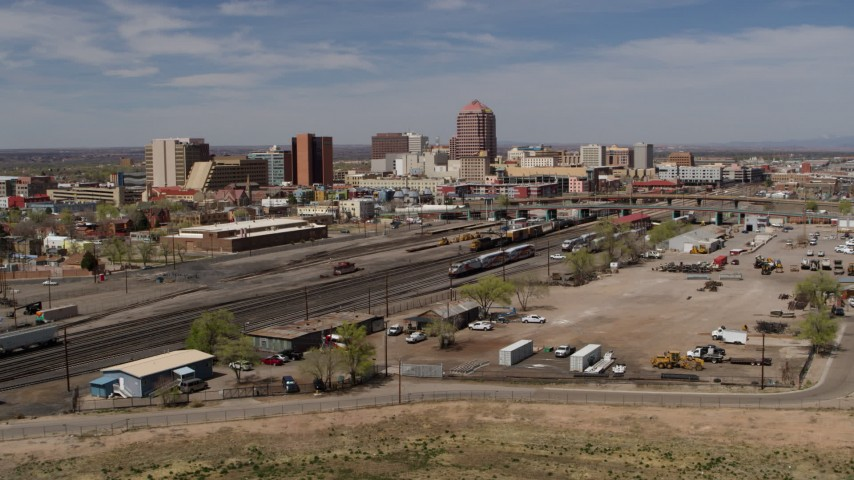 5.7K stock footage aerial video descend and fly away from train tracks with office buildings in the distance, Downtown Albuquerque, New Mexico Aerial Stock Footage | DX0002_124_037
