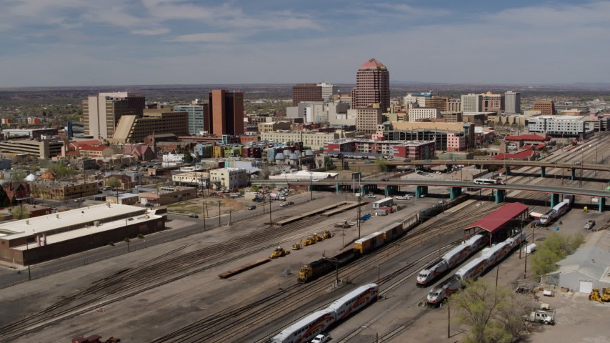 5.7K stock footage aerial video approach train tracks and office buildings in the distance, Downtown Albuquerque, New Mexico Aerial Stock Footage | DX0002_124_038