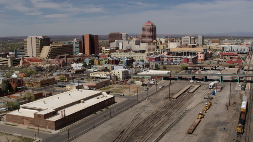 5.7K stock footage aerial video reverse view of distant office buildings seen from train tracks, Downtown Albuquerque, New Mexico Aerial Stock Footage | DX0002_124_039