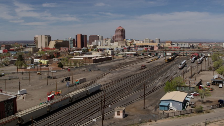 5.7K stock footage aerial video of distant office buildings seen from railroad tracks, Downtown Albuquerque, New Mexico Aerial Stock Footage | DX0002_124_040