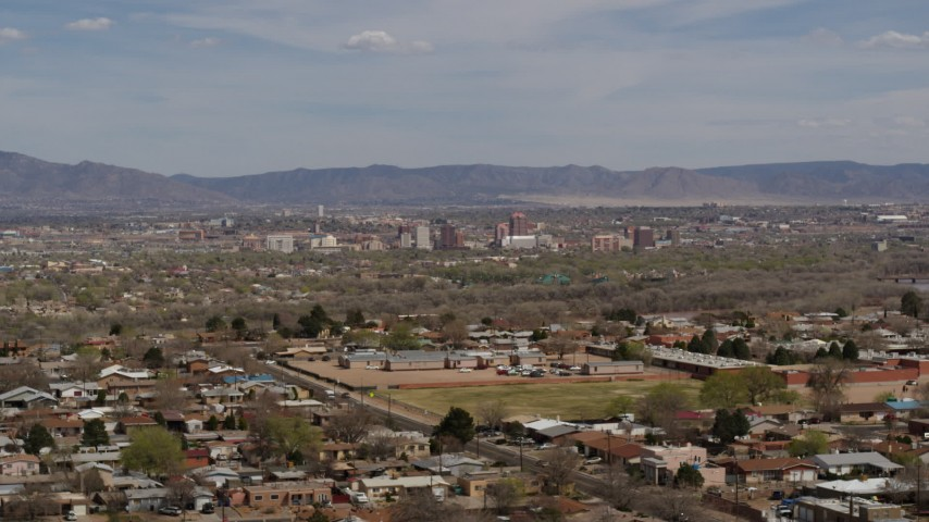 5.7K stock footage aerial video flying by suburban homes with a view of Downtown Albuquerque in the distance, New Mexico Aerial Stock Footage | DX0002_126_001