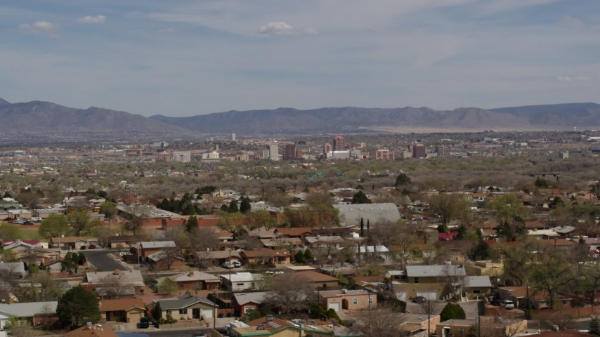 5.7K stock footage aerial video passing by suburban homes with a view of Downtown Albuquerque in the background, New Mexico Aerial Stock Footage | DX0002_126_002