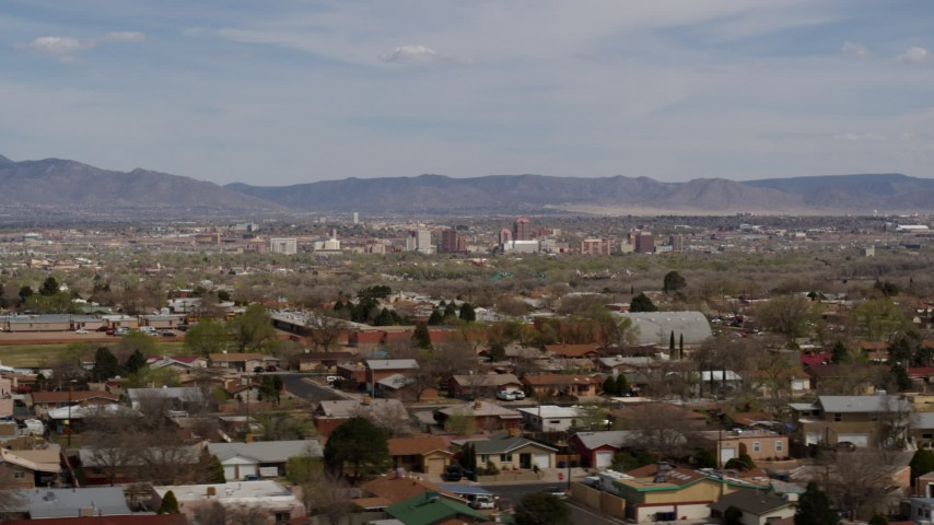 5.7K stock footage aerial video flyby suburban homes with a view of Downtown Albuquerque in the distance, New Mexico Aerial Stock Footage | DX0002_126_003
