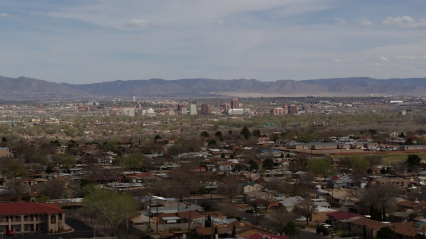 5.7K stock footage aerial video ascend past suburban homes with a view of Downtown Albuquerque in the distance, New Mexico Aerial Stock Footage | DX0002_126_004