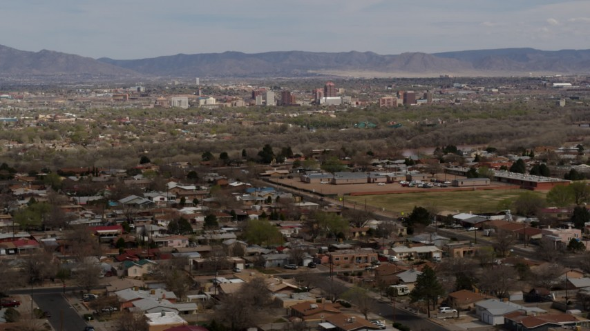 5.7K stock footage aerial video flying by a suburban neighborhood with a view of Downtown Albuquerque in the distance, New Mexico Aerial Stock Footage | DX0002_126_005