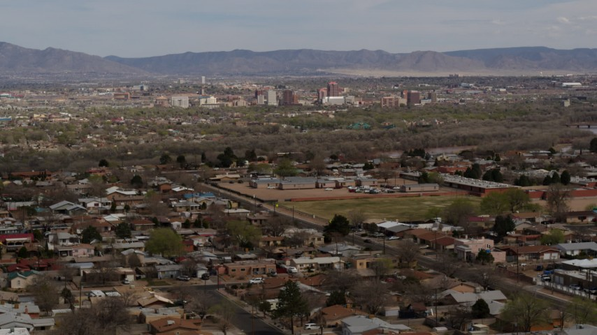 5.7K stock footage aerial video passing by a suburban neighborhood with Downtown Albuquerque in the distance, New Mexico Aerial Stock Footage | DX0002_126_006