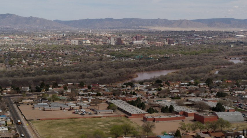 5.7K stock footage aerial video ascend over suburban neighborhood with Downtown Albuquerque beyond Rio Grande, New Mexico Aerial Stock Footage | DX0002_126_008