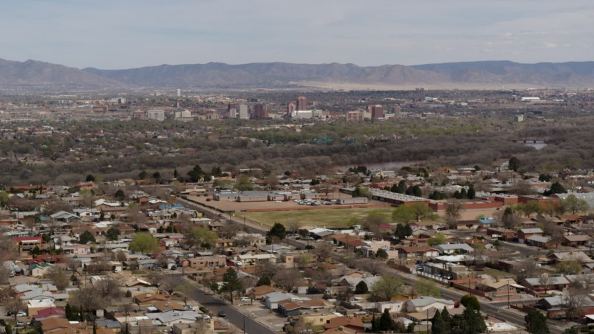 5.7K stock footage aerial video fly away from Downtown Albuquerque and Rio Grande, seen from suburban homes, New Mexico Aerial Stock Footage | DX0002_126_010