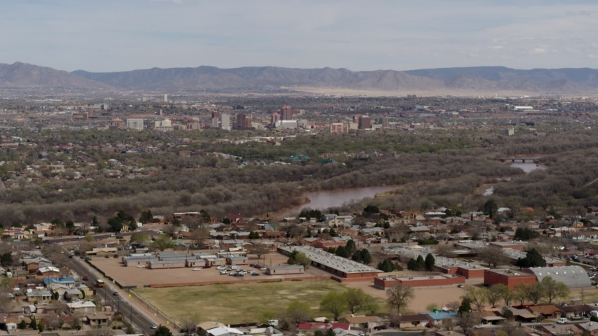 5.7K stock footage aerial video of Downtown Albuquerque and Rio Grande, seen while ascending from suburban homes, New Mexico Aerial Stock Footage | DX0002_126_012