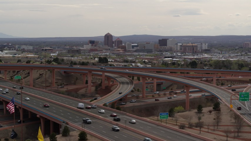5.7K stock footage aerial video of Downtown Albuquerque seen while flying by freeway interchange, New Mexico Aerial Stock Footage | DX0002_126_021