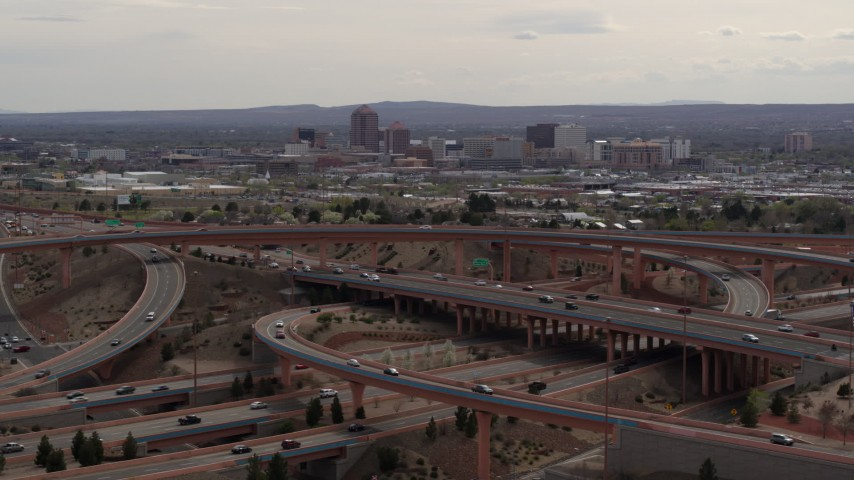 5.7K stock footage aerial video of Downtown Albuquerque seen while passing freeway interchange traffic, New Mexico Aerial Stock Footage | DX0002_126_023