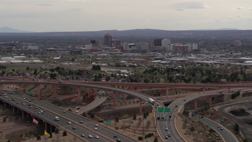 5.7K stock footage aerial video of Downtown Albuquerque seen while ascending near freeway interchange traffic, New Mexico Aerial Stock Footage | DX0002_126_024