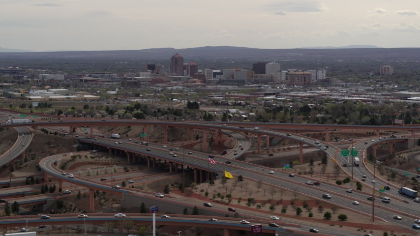 5.7K stock footage aerial video of Downtown Albuquerque seen while descending near freeway interchange traffic, New Mexico Aerial Stock Footage | DX0002_126_026