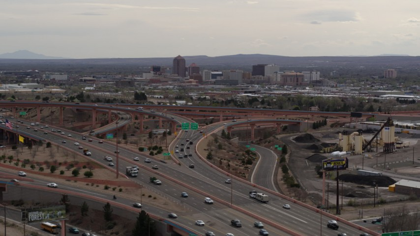 5.7K stock footage aerial video of Downtown Albuquerque buildings seen while descending past freeway interchange traffic, New Mexico Aerial Stock Footage | DX0002_126_028