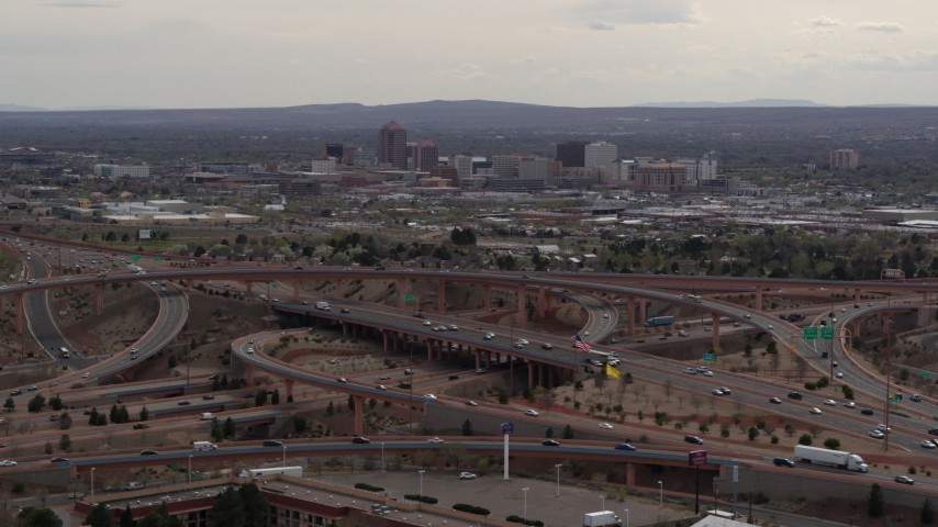 5.7K stock footage aerial video of Downtown Albuquerque buildings seen while flying by freeway interchange traffic, New Mexico Aerial Stock Footage | DX0002_126_029