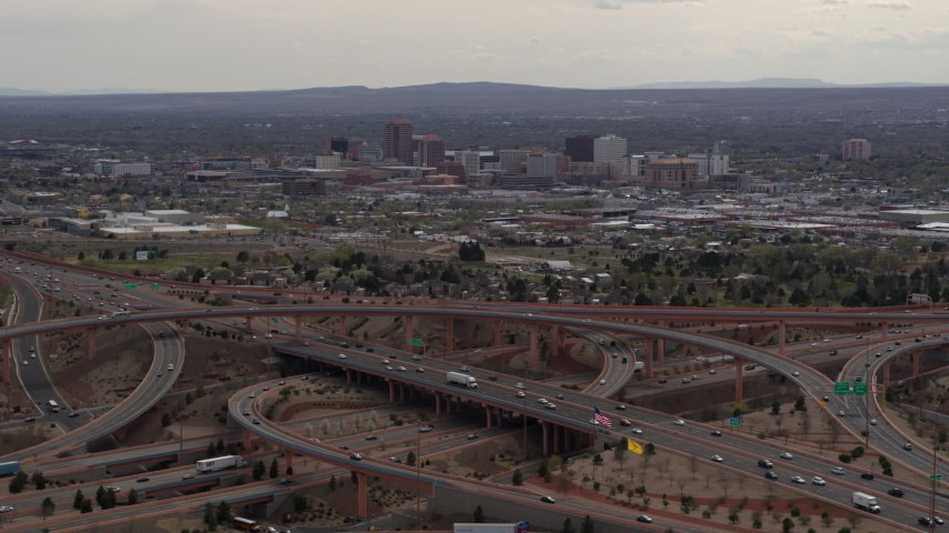 5.7K stock footage aerial video of Downtown Albuquerque buildings seen while passing freeway interchange traffic, New Mexico Aerial Stock Footage DX0002_126_030
