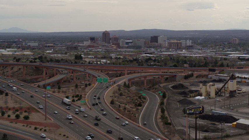 5.7K stock footage aerial video of Downtown Albuquerque buildings seen while descending by freeway interchange traffic, New Mexico Aerial Stock Footage | DX0002_126_031