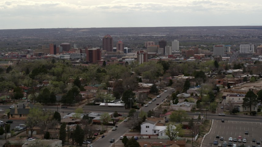 5.7K stock footage aerial video wide view of city's high-rises seen while flying by homes, Downtown Albuquerque, New Mexico Aerial Stock Footage | DX0002_126_043