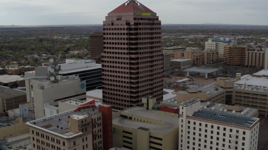 5.7K stock footage aerial video flying away from Albuquerque Plaza and neighboring city buildings, Downtown Albuquerque, New Mexico Aerial Stock Footage | DX0002_127_005