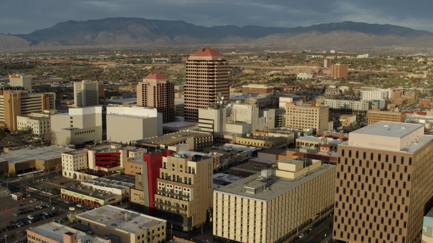 5.7K stock footage aerial video orbit and fly away from Albuquerque Plaza high-rise towering over city buildings, Downtown Albuquerque, New Mexico Aerial Stock Footage | DX0002_127_032