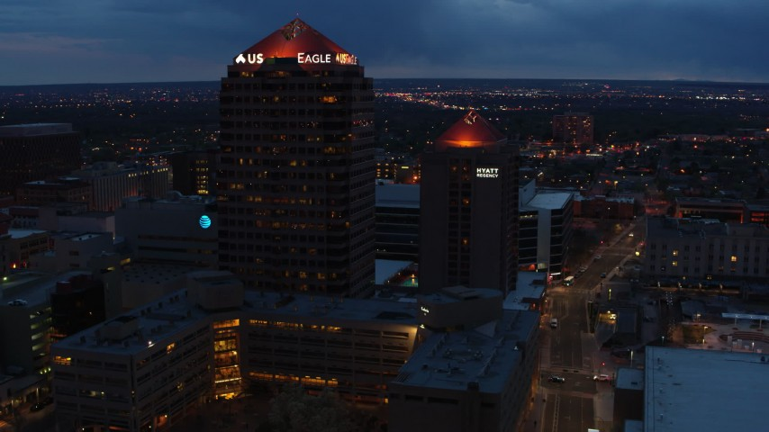5.7K stock footage aerial video orbit and fly away from office high-rise and hotel at twilight, Downtown Albuquerque, New Mexico Aerial Stock Footage DX0002_128_031 | Axiom Images