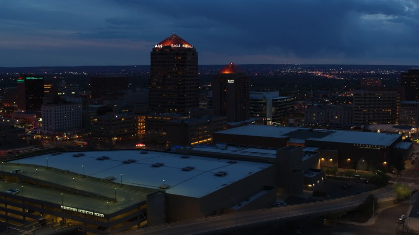 5.7K stock footage aerial video fly away from office high-rise, hotel, auditorium and reveal convention center at twilight, Downtown Albuquerque, New Mexico Aerial Stock Footage | DX0002_128_032