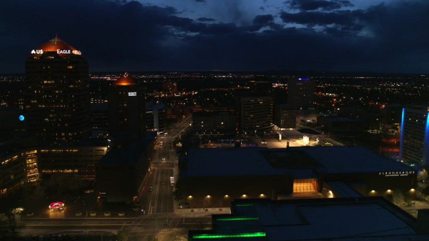 5.7K stock footage aerial video follow street between high-rise hotel and auditorium at twilight, Downtown Albuquerque, New Mexico Aerial Stock Footage | DX0002_128_040