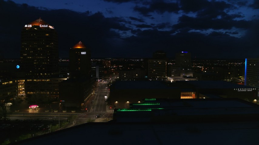 5.7K stock footage aerial video of a city street between high-rise hotel and auditorium at twilight during descent, Downtown Albuquerque, New Mexico Aerial Stock Footage | DX0002_128_049