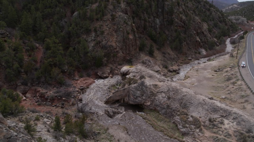 5.7K stock footage aerial video ascend and fly away from river rapids flowing through a rock formation in the mountains in New Mexico Aerial Stock Footage | DX0002_129_005