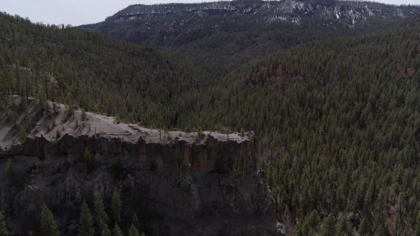 5.7K stock footage aerial video descend by the end of a rock formation jutting from a mountain in New Mexico Aerial Stock Footage | DX0002_129_016