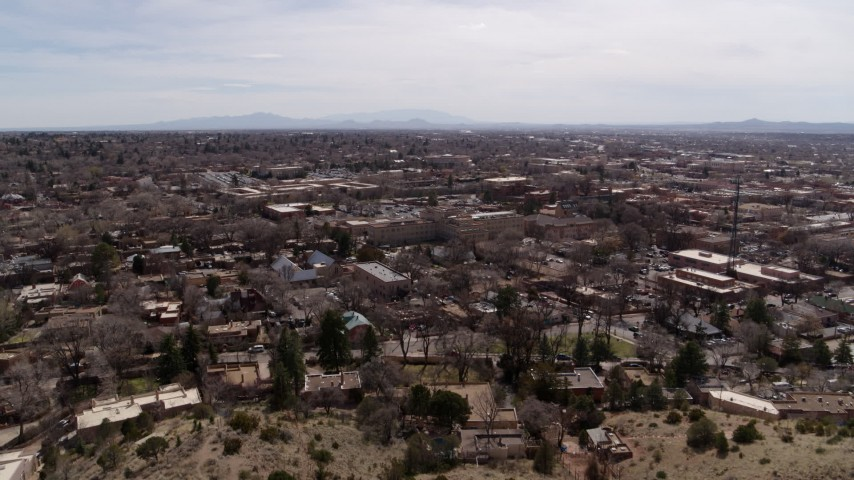 5.7K stock footage aerial video flying by the downtown area of Santa Fe during ascent, New Mexico Aerial Stock Footage | DX0002_129_017