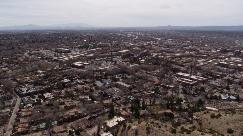 5.7K stock footage aerial video reverse view of the downtown area and surrounding city of Santa Fe, New Mexico Aerial Stock Footage | DX0002_129_020
