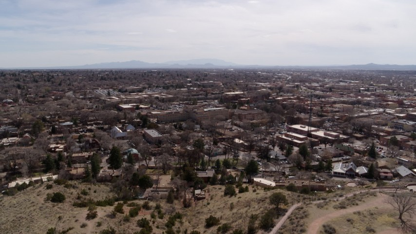 5.7K stock footage aerial video wide view of the downtown area, surrounding city of Santa Fe, New Mexico during descent Aerial Stock Footage | DX0002_129_026