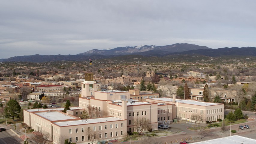 5.7K stock footage aerial video of passing the Bataan Memorial Building for wide view of downtown, Santa Fe, New Mexico Aerial Stock Footage | DX0002_131_015