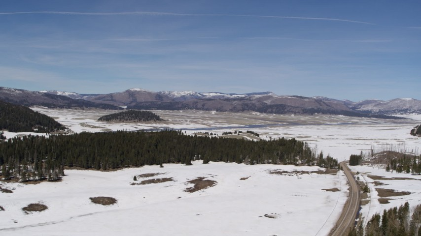 5.7K stock footage aerial video of distant mountains seen across a snowy valley, New Mexico Aerial Stock Footage | DX0002_134_015