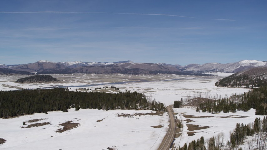 5.7K stock footage aerial video of a reverse view of distant mountains on the other side of a snowy valley, New Mexico Aerial Stock Footage | DX0002_134_016