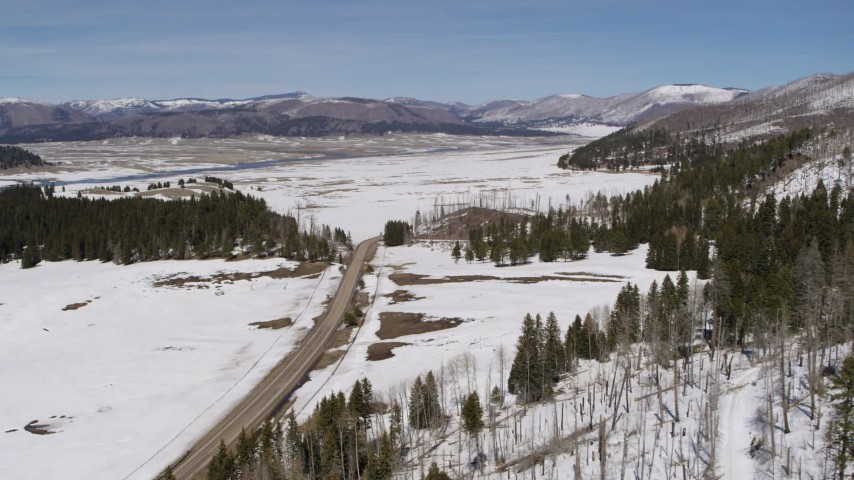 5.7K stock footage aerial video of a country road in snowy valley with view of mountains, New Mexico Aerial Stock Footage | DX0002_134_019