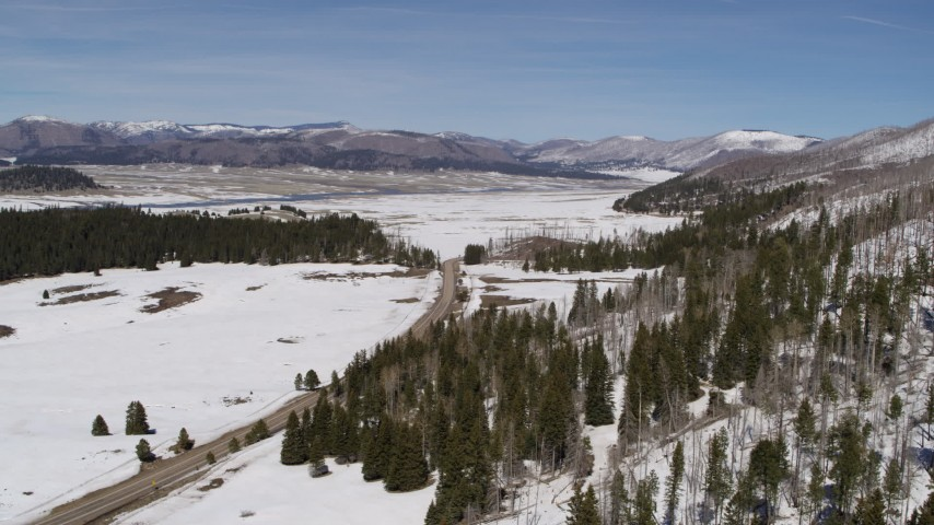 5.7K stock footage aerial video fly away from and near a country road in snowy valley with view of mountains, New Mexico Aerial Stock Footage | DX0002_134_020